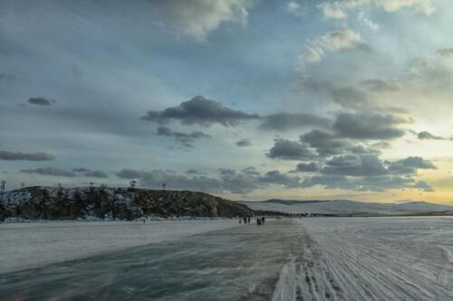Закат на ледовой переправе озеро Байкал, солнце сквозь тучи