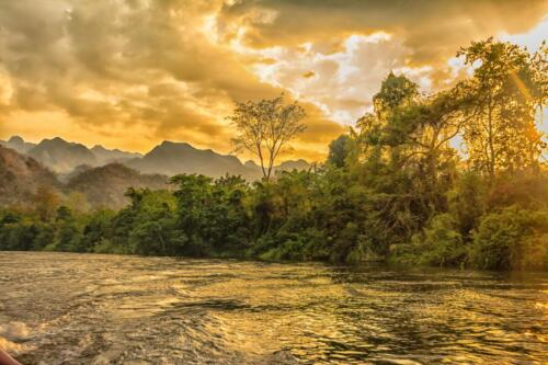 Burning sunset on the river in the jungle with the mountains as a backdrop