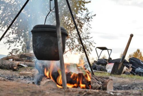 Котелок на костре, горят дрова в походном лагере